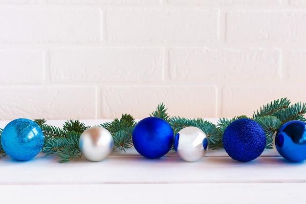 Composizione natalizia con palline blu e silfer e rami di abete su sfondo bianco muro di mattoni