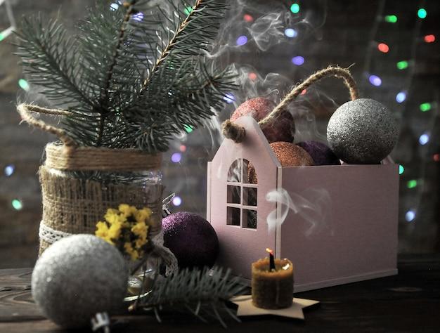 Composizione in natale con una candela, una casa e decorazioni natalizie su un tavolo