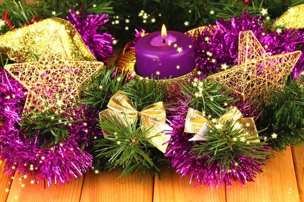 Composizione natalizia con candele e decorazioni nei colori viola e oro su fondo in legno