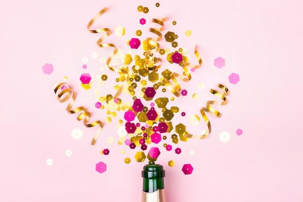 Composizione natalizia con scintillii dorati di bottiglia di champagne su sfondo rosa pastello. concetto creativo di vacanza.