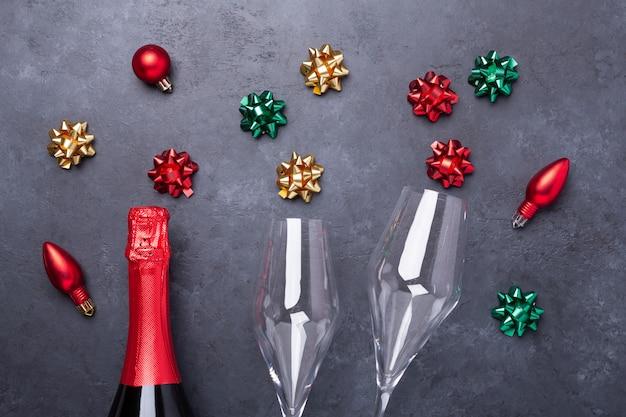 Composizione di natale con bicchieri di champagne e bottiglia e fiocchi colorati