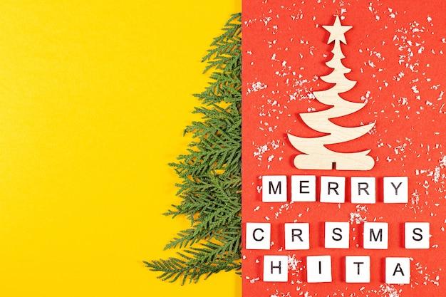 Composizione in natale con rami di conifere su sfondo di carta gialla con spazio per il testo. vista dall'alto. concetto di nuovo anno