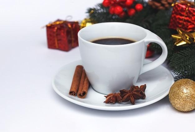 Composizione natalizia con tazza di caffè, spezie e decorazioni natalizie.