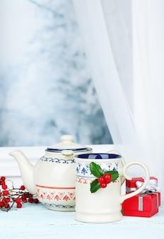 Composizione natalizia con tazza e teiera di bevanda calda, su tavola di legno