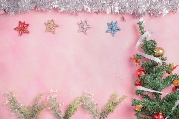 Composizione in natale con decorazioni e confezione regalo con fiocchi su sfondo rosa pastello. inverno, concetto di nuovo anno. appartamento laico, vista dall'alto, copia dello spazio.