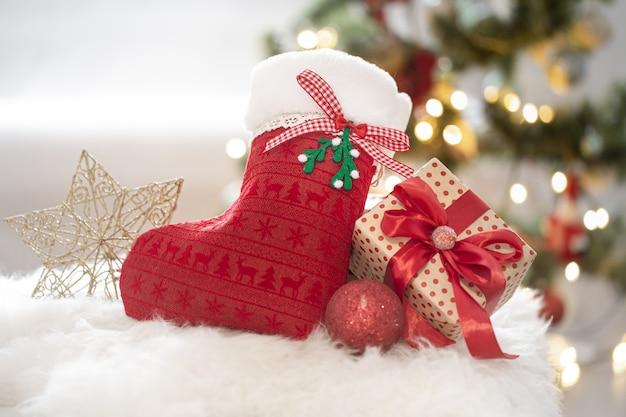 Composizione natalizia con calzino decorativo e confezione regalo in un'accogliente atmosfera casalinga
