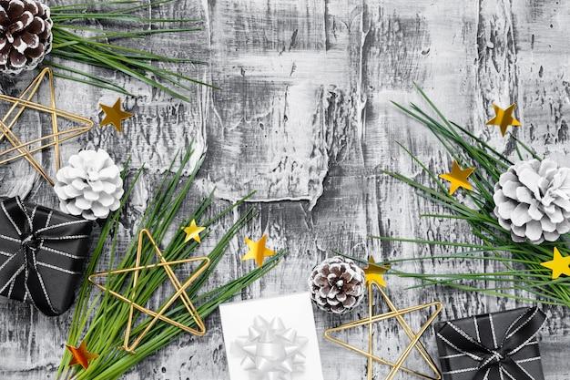 Composizione di natale con rami di abete, stelle dorate e scatole regalo