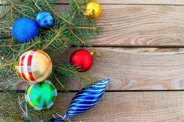 Composizione natalizia con rami di abete e decorazioni natalizie su tavola di legno. vista dall'alto, copia spazio