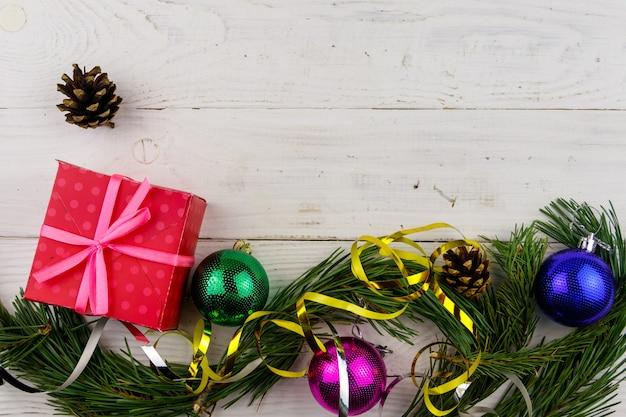 Composizione natalizia con rami di abete, confezione regalo e decorazioni natalizie su tavolo di legno bianco. vista dall'alto, copia spazio