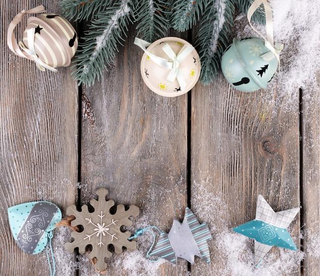 Composizione natalizia con abete, giocattoli e neve su fondo in legno