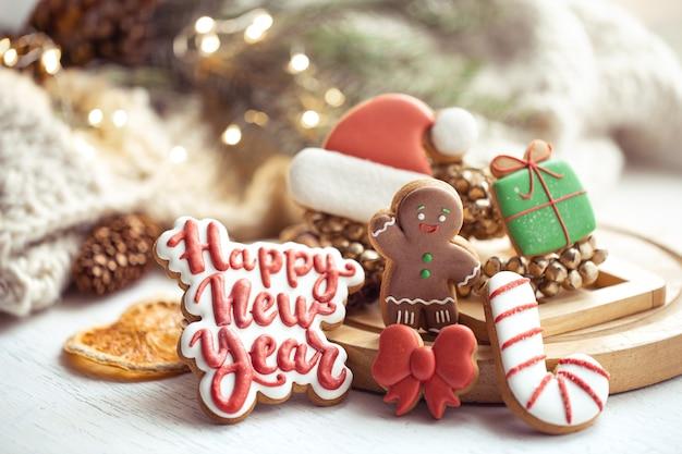 Composizione natalizia con biscotti di panpepato glassati fatti a mano con auguri di felice anno nuovo. home concetto di intimità invernale.