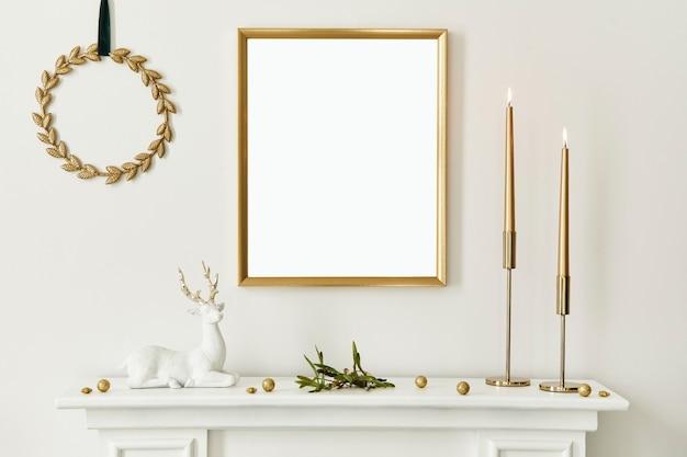 Composizione natalizia con cornice per poster finta in oro, camino bianco e decorazione. alberi di natale e ghirlande, candele, stelle, accessori leggeri ed eleganti. modello.
