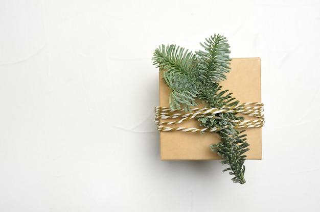 Composizione in natale con rami di abete verde e confezione regalo kraft su fondo di legno bianco con copyspace.
