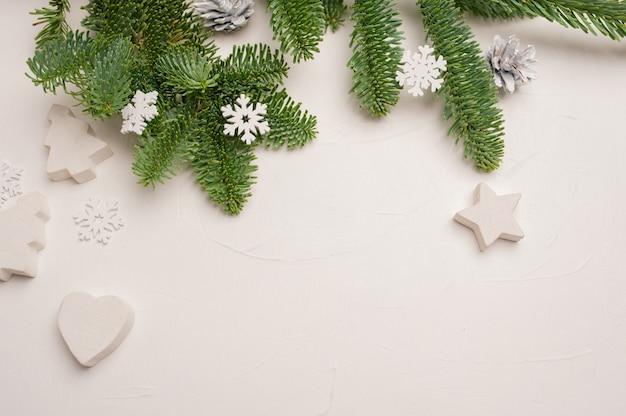 Composizione natalizia con rami di abete verde e decorazioni in legno bianco di stelle e cuori