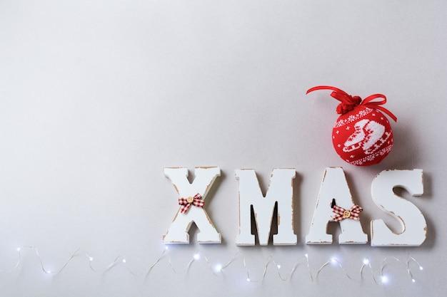 Composizione in natale con lettere xmas e decorazioni di capodanno su grigio