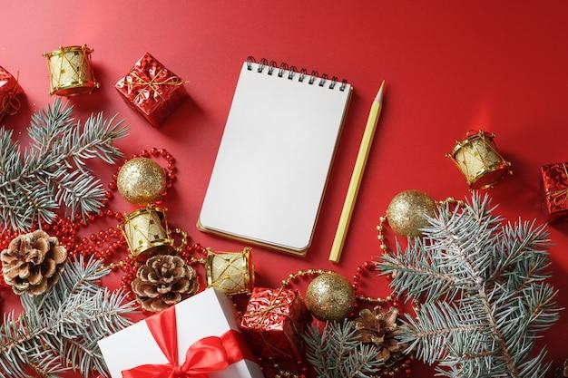 Composizione in natale con blocco note e una matita per scrivere auguri con addobbi per l'albero di natale su fondo rosso