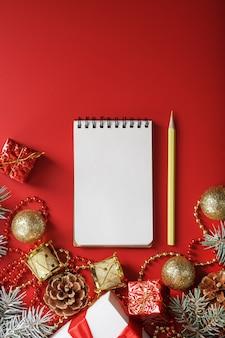 Composizione natalizia con blocco note e matita per scrivere auguri con addobbi natalizi