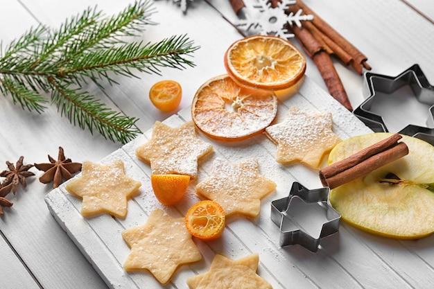 Composizione natalizia con biscotti crudi e cannella su tavola di legno