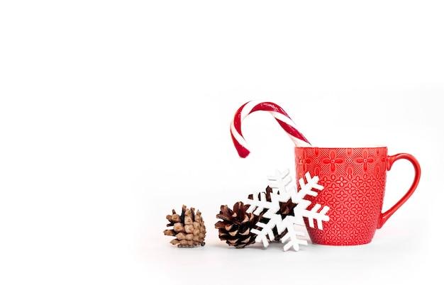 Composizione in natale con tazza rossa, pigne e fiocco di neve