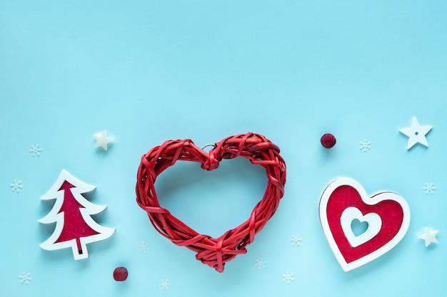 Composizione in natale con decorazioni rosse e bianche su superficie blu pastello, vista dall'alto, copia dello spazio. buon natale e buone feste biglietto di auguri, telaio, banner, piatto laici