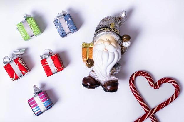 Composizione natalizia con babbo natale o gnomo, regali, bastoncini di zucchero natalizi a forma di cuore, palline viola e argento, pigne, copia spazio. può essere usato come biglietto di capodanno e natale