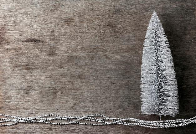 Composizione in natale con l'albero di natale d'argento su fondo di legno. natale, concetto di capodanno