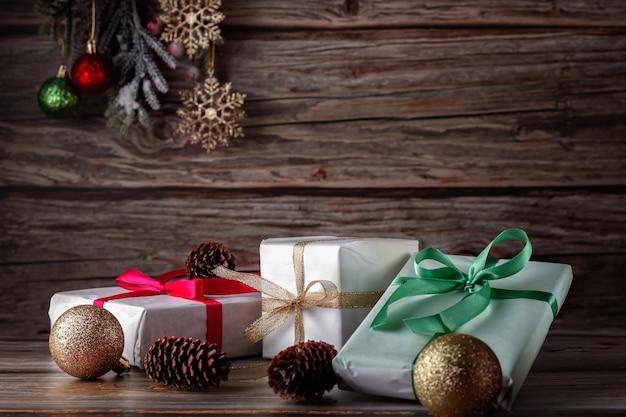 Composizione in natale con piccoli doni, nastri, palle di natale e ramo di abete