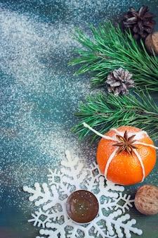 Composizione natalizia con mandarino, candele, fiocchi di neve e rami di abete. con spazio per il testo