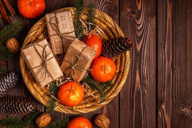 Composizione in natale con mandarini, scatole regalo, coni