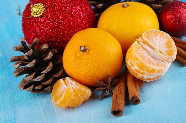Composizione di natale con mandarini su tavola di legno su sfondo blu