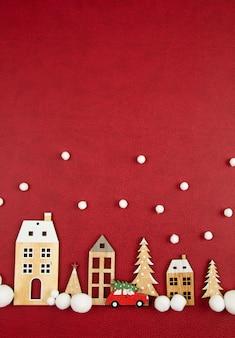 Composizione in natale con le case di legno del giocattolo sopra i precedenti rossi