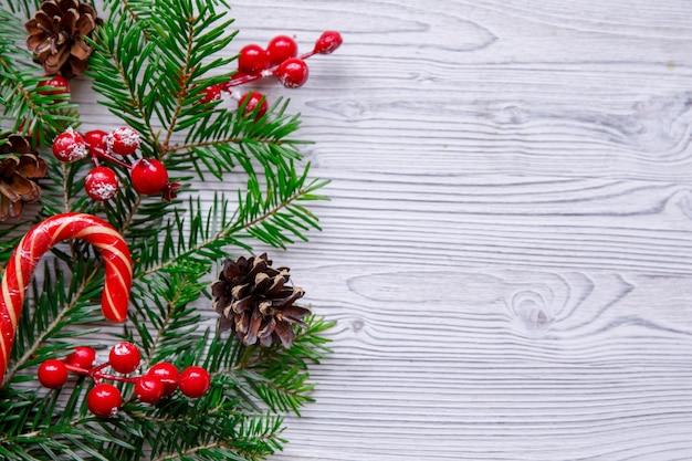 Composizione in natale con albero di natale e bacche rosse sul tavolo bianco
