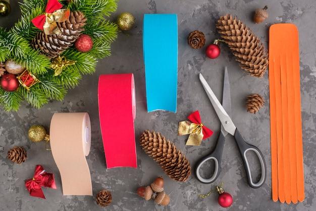 Composizione natalizia di nastro per kinesiologia ghirlanda, abete, pigne, palline, nastri e rotoli per atleti e forbici