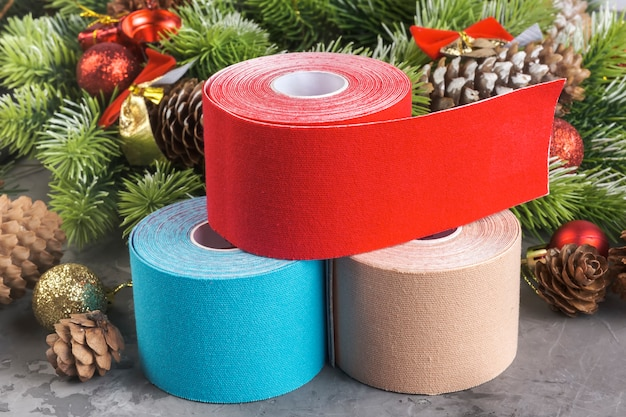 Composizione natalizia di nastro kinesiologico per atleti in ghirlanda, abete, pigne, palline, nastri e rotoli