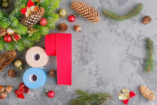 Composizione natalizia di nastro kinesiologico ghirlanda, abete, pigne, palline, nastri e rotoli