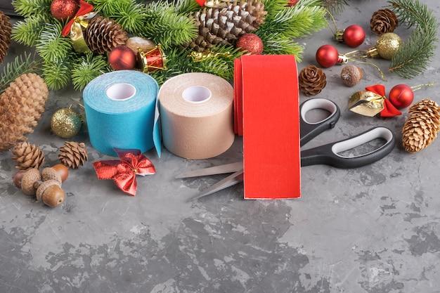 Composizione natalizia di ghirlanda, abete, pigne, palline, nastri e nastro di cinesiologia e forbici rotoli di stack