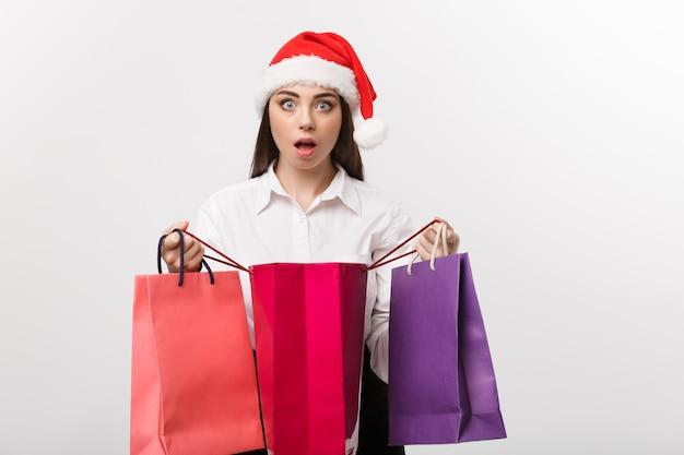 Concetto di natale bella donna d'affari caucasica scioccante con regalo all'interno del sacchetto della spesa