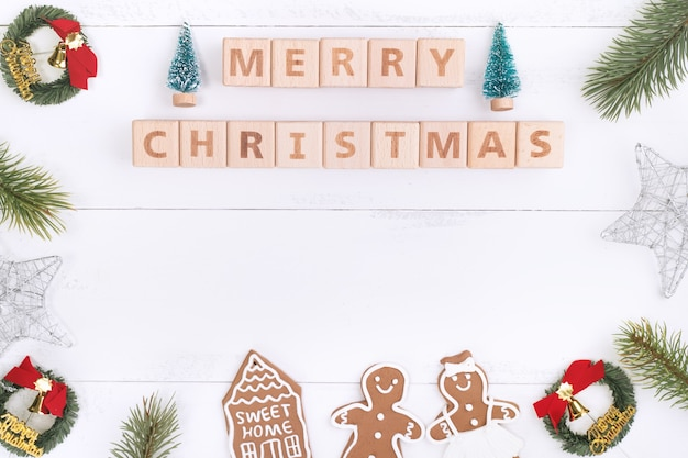 Natale concetto composizione decorazione oggetti, abete ramo corona, panpepato uomo biscotto isolato su bianco tavolo in legno, vista dall'alto, laici piatta