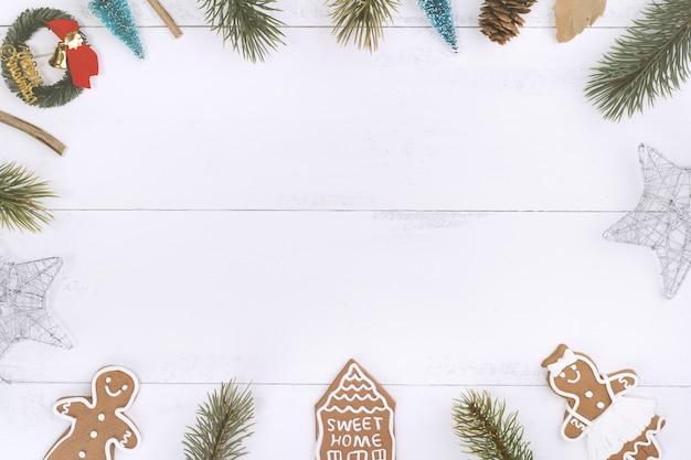 Natale concetto composizione decorazione oggetti, abete ramo corona, panpepato uomo biscotto isolato su bianco tavolo in legno, vista dall'alto, piatto laici