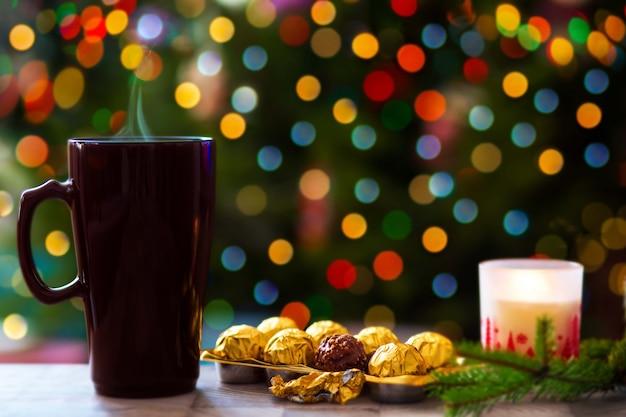 Concetto di natale una tazza di cioccolata calda sullo sfondo di un albero di natale con luci