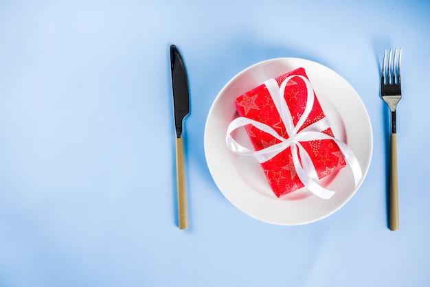 Concetto di natale, pranzando sfondo con piastra, forchetta, coltello e confezione regalo in imballaggio festivo, sfondo azzurro copia spazio sopra