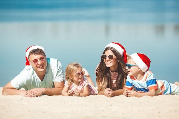Concetto di natale. famiglia che indossa i cappucci di natale in spiaggia
