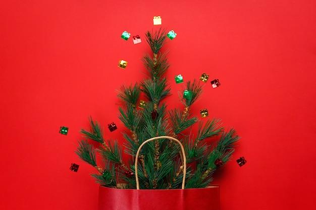 Concetto di natale. rami di abete rosso verde in un pacchetto di carta rossa su rosso con coriandoli. lay piatto.