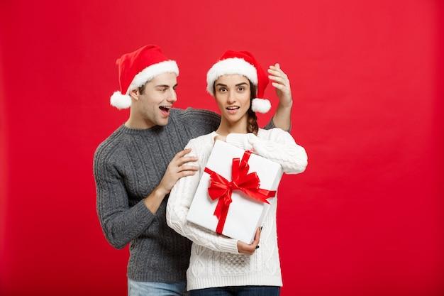 Concetto di natale - bel giovane ragazzo in maglione sorprende la sua ragazza con un regalo bianco.