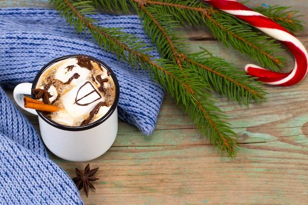 Concetto di natale, cioccolata calda o cacao con marshmallow e spezie, regali di natale, bastoncini di zucchero, ramo di albero di natale e pigne, sul vecchio tavolo in legno rustico.