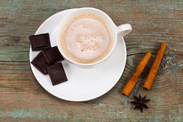 Concetto di natale, cioccolata calda o cacao con spezie su fondo di legno.
