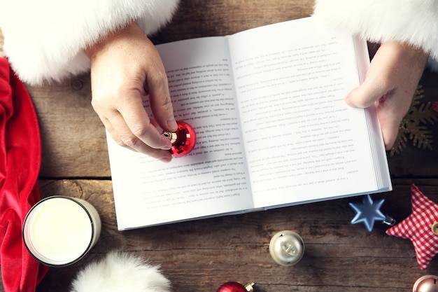 Concetto di natale. mani di babbo natale con libro e decorazioni natalizie sul tavolo di legno, primo piano