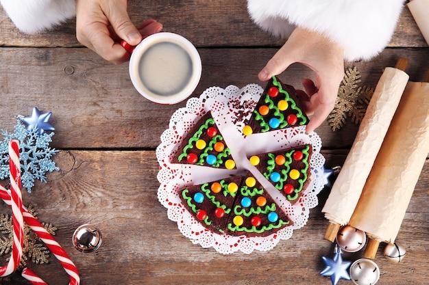 Concetto di natale. babbo natale mangia. le mani di babbo natale prendono un pezzo di torta al cioccolato e una tazza di caffè, da vicino