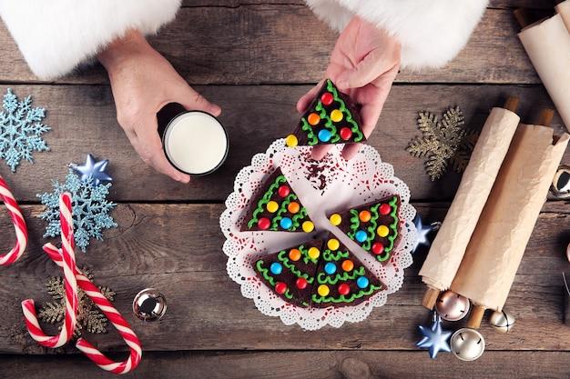 Concetto di natale. babbo natale mangia. le mani di babbo natale prendono un pezzo di torta al cioccolato e un bicchiere di latte, da vicino