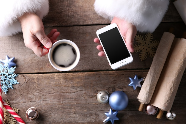 Concetto di natale. babbo natale prende lo smartphone in mano sul tavolo di legno da vicino